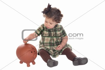 Baby girl inserting a coin into a piggybank