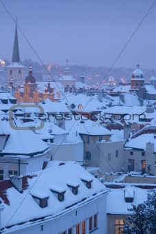 prague - winter view of mala strana rooftops covered with snow