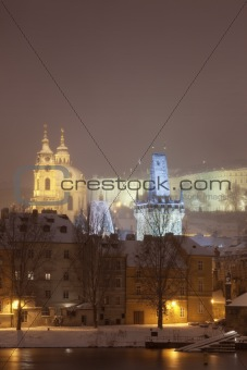 charles bridge tower and st. nicolaus church during heavy snowfall