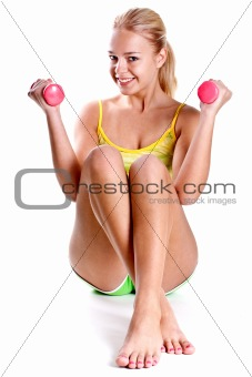 pink dumbbells in the hands of women