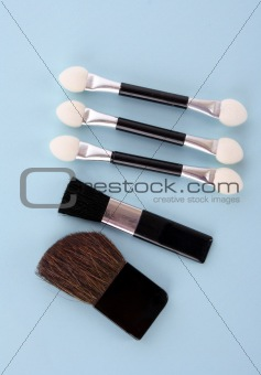 Cosmetic brushes on orange background