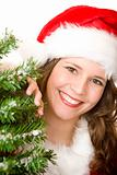 Young smiling Santa Woman standing beside Christmas tree