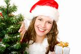 Young smiling Santa Woman near fir tree holds Christmas gift in