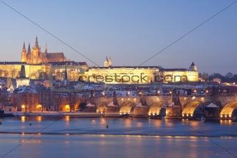 prague in winter - charles bridge and hradcany castle at dusk