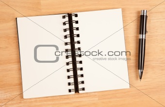 Blank Spiral Note Pad and Pen on Wood Background.