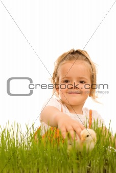 Little girl catching the small Easter chicken