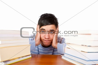 Young handsome male student sitting frustrated between study boo