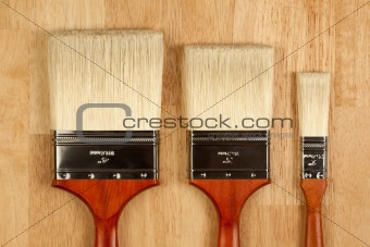 Three Different Sized New Paint Brushes on a Wood Surface.