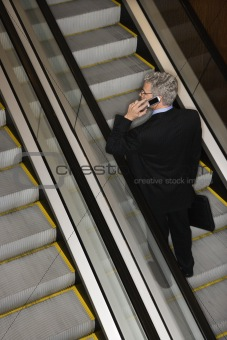 Businessman on Escalator with Cellphone