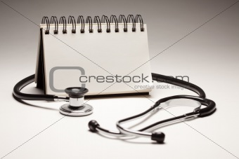 Blank Spiral Note Pad and Black Stethoscope on a Gradated Background.
