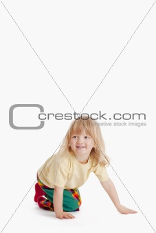 boy with long blond hair on the floor smiling isolated on white