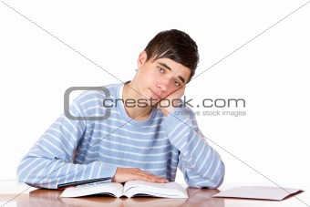 Tired handsome male student sitting on desk reading study books