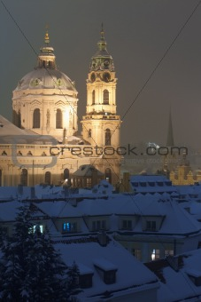 prague - view of snowy rooftops and st. nicolaus church in winter