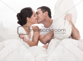 Couple kissing and playing on bed in bedroom, in passion
