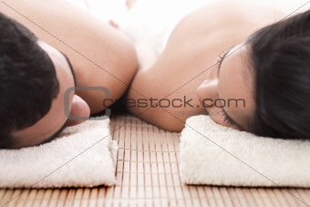 Young man and woman lying on towel to take spa