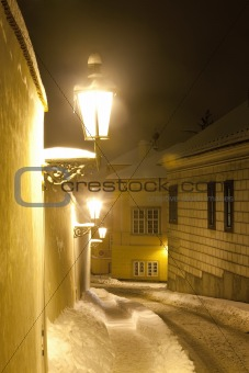 prague - narrow street at hradcany with gas lanterns in winter