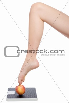 womans leg standing with the toe on an apple and a scale