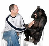 Portrait of mid adult man tickling chimpanzee