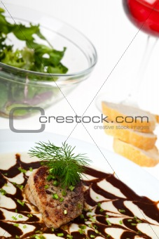 small veal steak on a bed of sauce