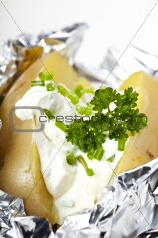closeup detail of a baked potato with sour cream