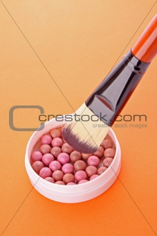 cosmetic brush and rouge  on the orange background
