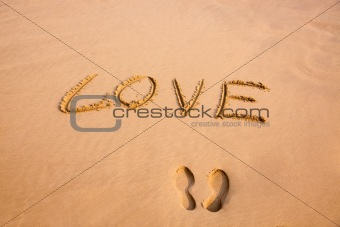 Footprint and handwriting Love in the sand on a beach