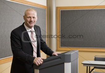 Business Man Standing at Podium Smiling