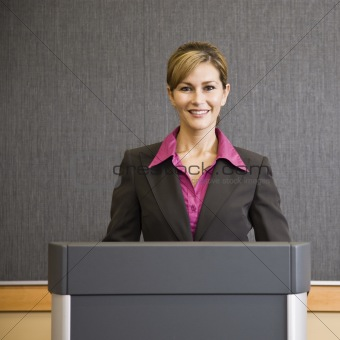 Woman Smiling Behind Podium