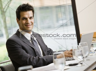 Man in Business Suit Smiling with laptop