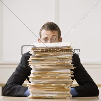 Businessman Behind Stack of File Folders