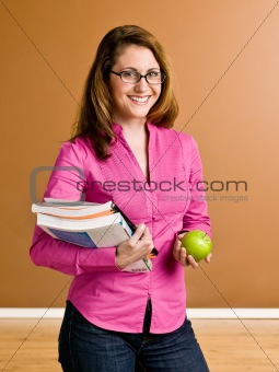 Confident woman holding apple and school books