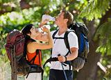 Couple with backpacks drinking water