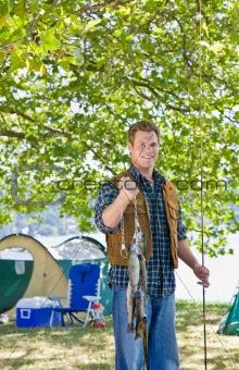 Fisherman carrying fish at campsite