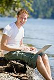 Man using laptop near stream