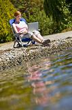 Woman using laptop near stream