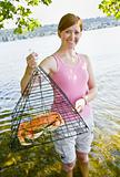 Woman holding crab in trap