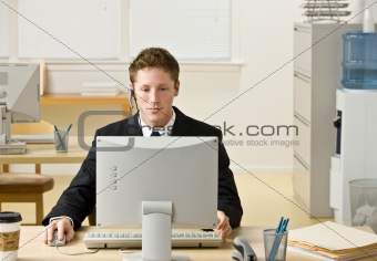 Businessman in headset working at computer