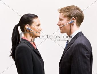 Business people in headsets standing face to face