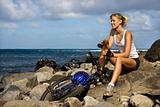 Attractive Young Woman Sitting With Bicycle on Rocky Beach