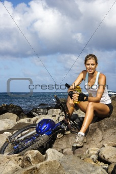 Attractive Young Woman Sitting With Bicycle on Rocky Coast