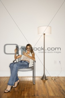 Attractive Young Woman Reading in Chair