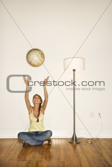 Attractive Young Woman Smiling and Sitting Tossing a Globe