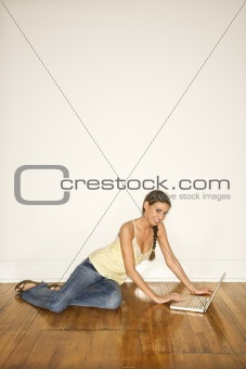Attractive Young Woman Smiling Sitting on Floor with Laptop