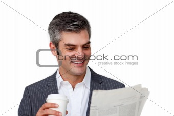 Charismatic businessman drinking a coffee while reading a newspa