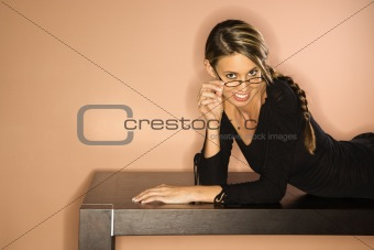 Attractive Young Woman Looking Over Her Glasses Smiling