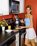 Attractive Young Woman in Kitchen Cooking Breakfast