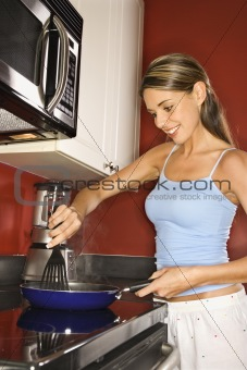 Attractive Young Woman in Kitchen Cooking