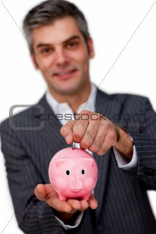 Charismatic male executive saving money in a piggybank