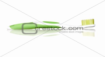 Green toothbrush with reflection on the floor