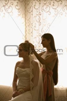 Bridesmaid placing veil.
